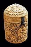 This cylindrical pyxis - a kind of casket - was carved in 968 for Prince al-Mughira (son of the deceased Caliph Abd al-Rahman III and half-brother of the reigning Caliph al-Hakam). It is the finest example of the luxury ivory objects made for the members of the court of Madinat al-Zahra (the caliph's residence and city of government, established near Cordoba in 936).<br/><br/>  Its four richly-decorated medallions are linked by borders of delicately pierced foliage, and this composition is reflected on the lid, whose medallions feature peacocks, falcons, lions, and a rider. There are four scenes on the body of the box. In one of these, a lutanist is flanked by two cross-legged figures who look at each other rather suspiciously.<br/><br/>  One holds a fan, the other a bottle (an emblem often associated with the king), and a braided vegetal scepter of the kind used by the Umayyad Dynasty. The other images, such as that of a bull attacked by a lion, are all doubled. Some curious little scenes show back-to-back figures stealing eggs from falcons' nests, with dogs biting their ankles, and the final medallion portrays riders picking bunches of dates.